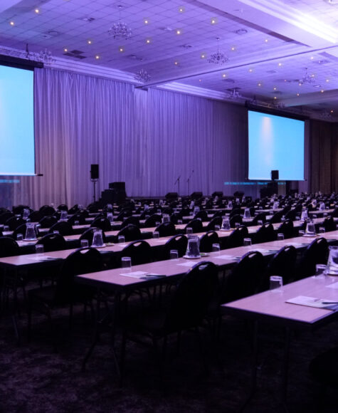 birchwood's OR tambo centre, rows of long tables and chairs in front of projector screens
