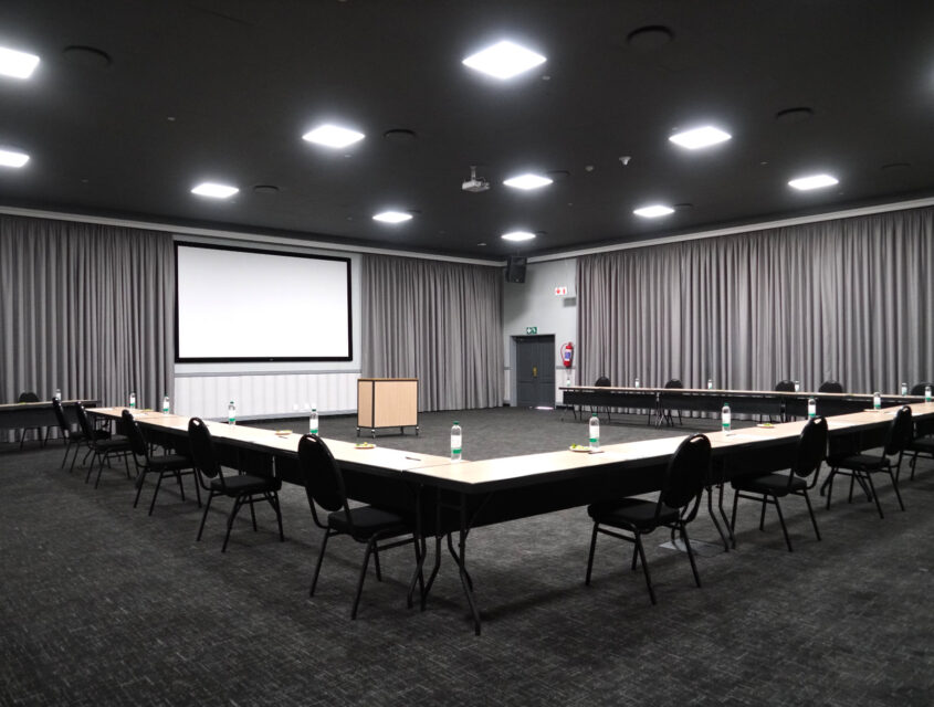 U-shaped table with chairs facing a blank projector screen