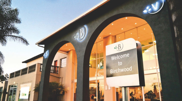 "birchwood hotel from outside with ""welcome to birchwood"" sign"