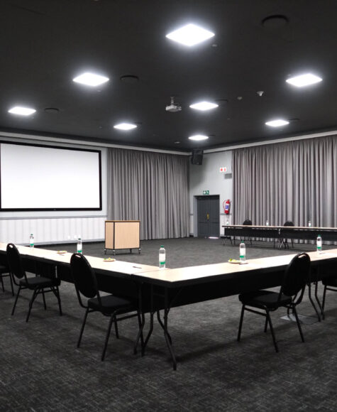 Conference room with tables and chairs set for social distancing